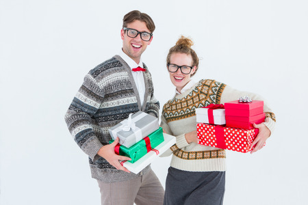 cheesy grin: Geeky hipster couple holding presents on white background