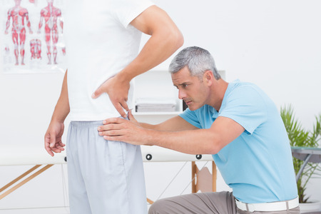 posture correction: Doctor examining his patient back in medical office Stock Photo