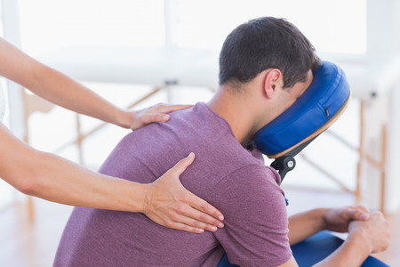 massage chair: Man having back massage in medical office