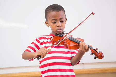 Focus pupil playing violin in classroom at elementary school