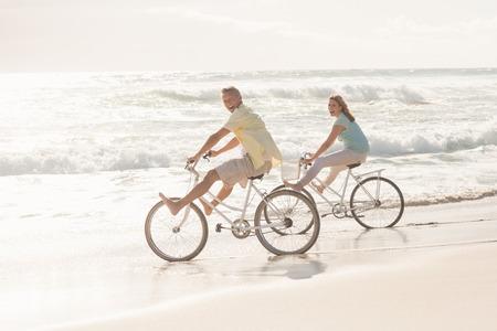 bicicleta: Feliz pareja en un paseo en bicicleta en la playa