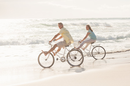 Happy couple on a bike ride at the beach