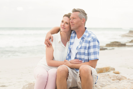 freedom couple: Casual couple sitting on rock at the beach