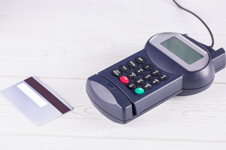pin entry: Pin terminal and credit card on a wooden table Stock Photo