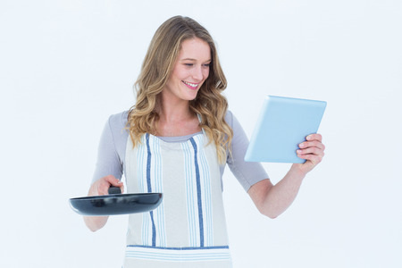 Smiling woman holding frying pan and tablet pc on white background photo
