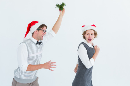 Geeky hipster running away from a man with mistletoe on white background photo
