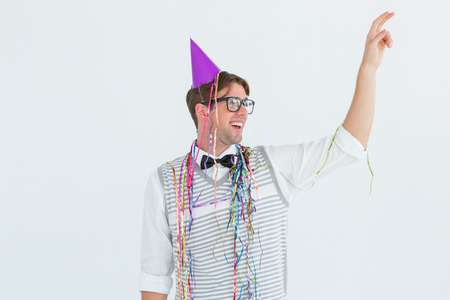 cheesy grin: Geeky hipster pointing something on white background Stock Photo