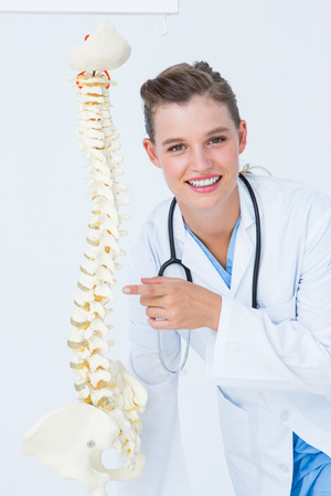 anatomical: Smiling doctor pointing an anatomical spine on white background