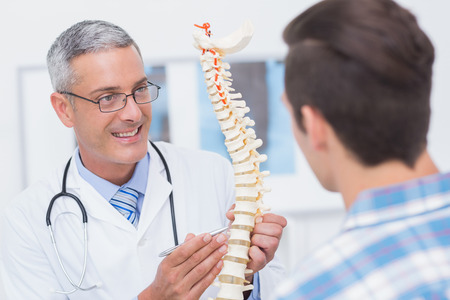 Doctor showing anatomical spine to his patient in medical office 스톡 콘텐츠