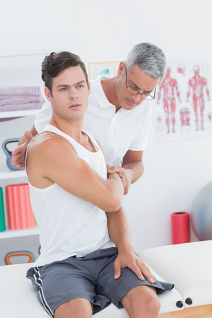 physical pressure: Doctor stretching a young man arm in medical office
