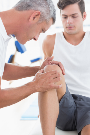 body check: Doctor examining his patient knee in medical office Stock Photo