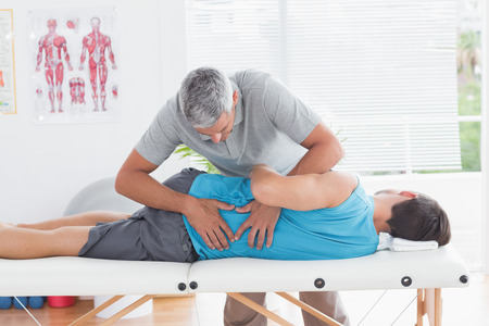 Doctor examining man back in medical office photo