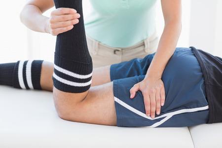 Doctor examining man leg in medical office