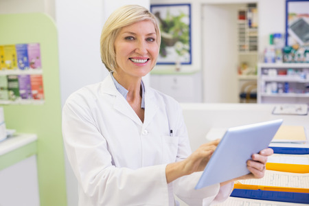 Junior pharmacist using tablet pc at the hospital pharmacy photo