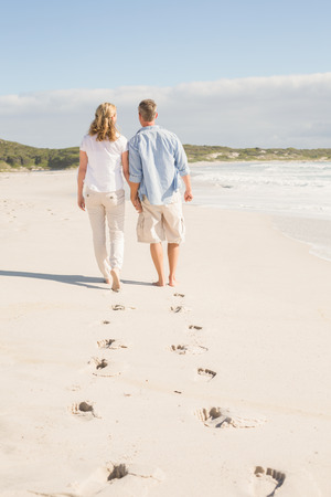 Happy couple walking holding hands at the beach Stock Photo