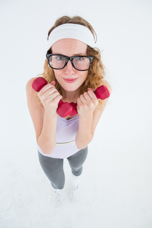 geeky: Geeky hipster lifting dumbbells on white background