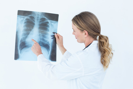 Focused doctor looking at xray on white background photo