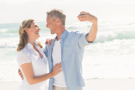 Happy couple taking a selfie at the beach photo