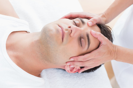holding on head: Man receiving head massage in medical office