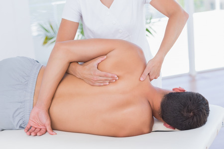massage table: Physiotherapist doing back massage to her patient in medical office Stock Photo