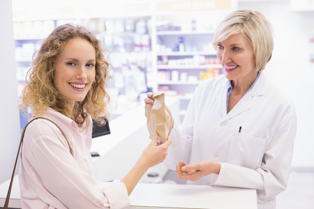 Pharmacist giving bag paper to costumer at pharmacy photo