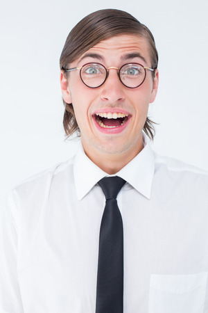 cheesy grin: Geeky businessman smiling at camera on white background