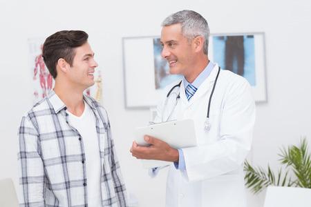 consulta médica: Doctor que muestra el portapapeles para su paciente en el consultorio médico