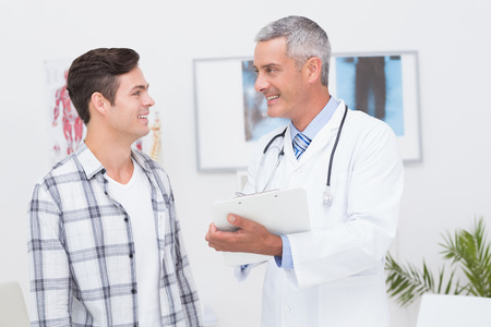 Doctor showing clipboard to his patient in medical office