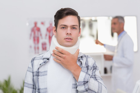 neck brace: Patient with neck brace looking at camera in medical office