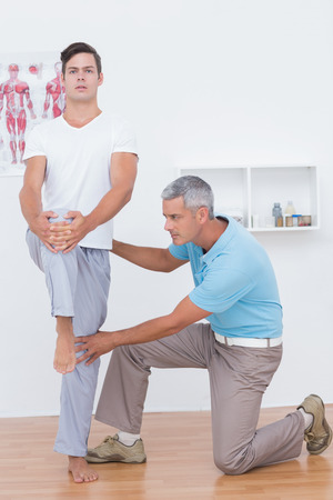 postural integration: Doctor examining his patient legs in medical office Stock Photo