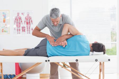 dolor de espalda: Doctor que examina al hombre de vuelta en el consultorio médico Foto de archivo