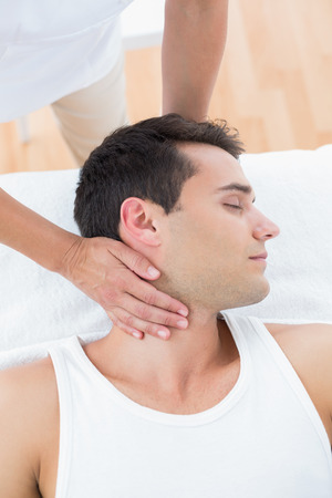 turning table: Man receiving neck massage in medical office
