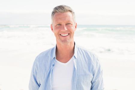 Knappe man die lacht op camera op het strand