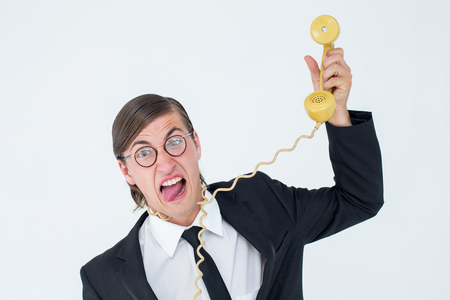 phone cord: Geeky businessman being strangled by phone cord on white background Stock Photo