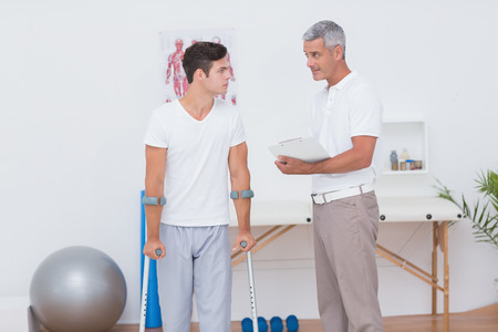 retraining: Man with crutch speaking with his doctor in medical office Stock Photo