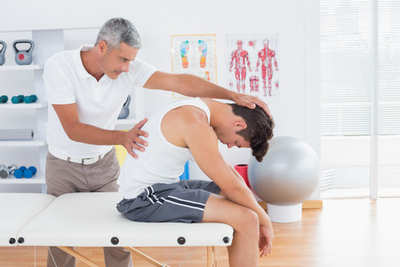 Doctor stretching a young man back in medical office Stock Photo