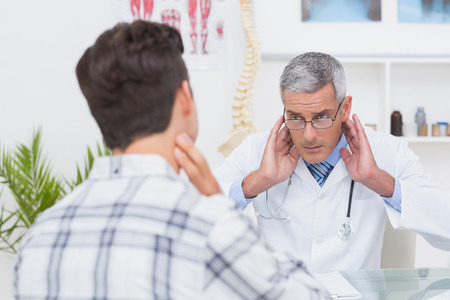Doctor examining patient with neck ache in medical office