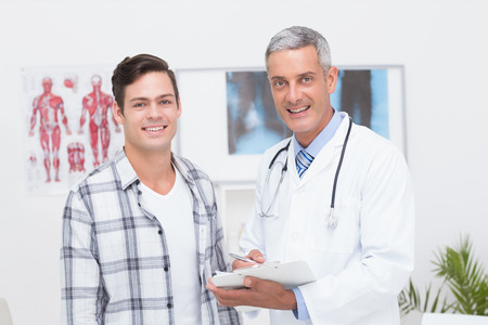 happy patient: Doctor showing clipboard to his patient in medical office