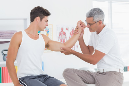 joint mobilization: Doctor examining his patient arm in medical office Stock Photo