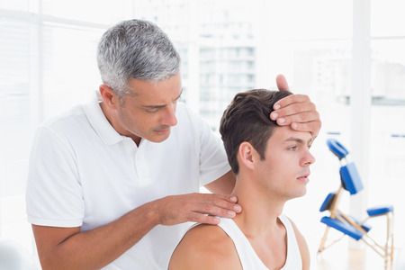 treatments: Doctor doing neck adjustment in medical office