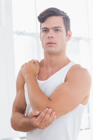 elbow pain: Young man suffering from elbow pain in medical office