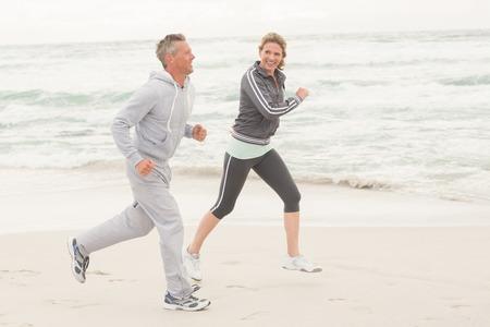 Fit paar joggen samen op het strand Stockfoto