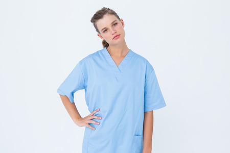 inquiring: Serious nurse in blue scrubs posing with hand on hip on white background Stock Photo