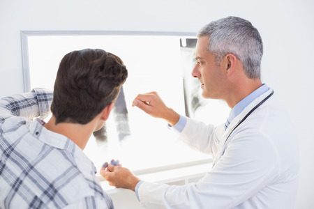 young adult men: Doctor looking X rays with his patient in medical office