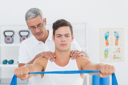postural integration: Doctor examining his patient back in medical office Stock Photo
