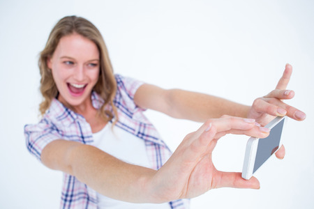 cheesy grin: Pretty hipster taking selfie with smartphone on white background