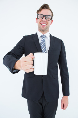 geeky: Happy geeky businessman holding coffee mug on white background