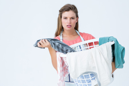 perplex: Hipster woman holding laundry basket on white background Stock Photo