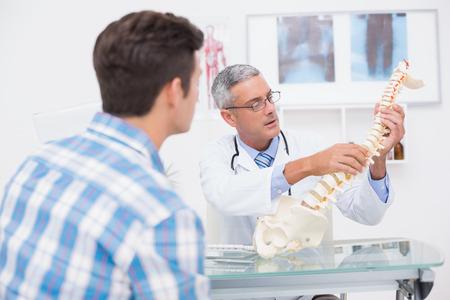 espina dorsal: Médico explicando columna vertebral anatómica a su paciente en el consultorio médico Foto de archivo