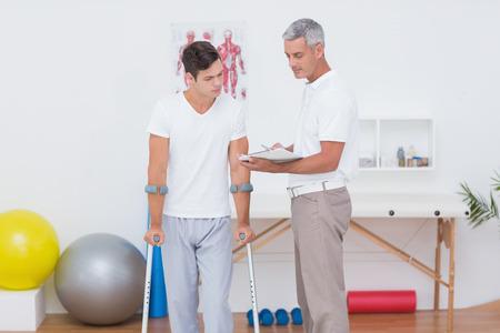 fisioterapia: Doctor que muestra el portapapeles para su paciente con la muleta en el consultorio médico
